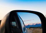The Mission Mountains and a full moon reflected in the side mirror of a truck in the National Bison range in Montana
