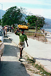 Lady carrying a tray of oranges on her head. Images of the capital,Port au Prince, Haiti 1975