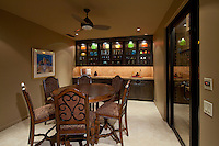 Round table with 6 chairs are seen in wine room with walkin wine cellar