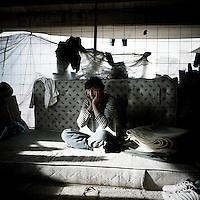 16 year old Hababullah sits on his bed in an abandoned building where he squats. Patras is home to about 3,000 illegal immigrants. Most of them are Afghans, although there are also some Iranians and Uzbeks. They stop in Patras to try and find passage to various European destinations by hiding in ships, containers and trucks parked in the port. If they are lucky they will make it to their destination. Many of them live in shacks made from cartons, plastic and wood they found on the beach. To shelter from the cold they also squat in abandoned buildings, living without water and electricity. The living conditions are inhumane and unhygienic.