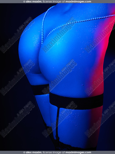 Sexy woman wearing stockings with garters, closeup of buttocks with pearl beads in dramatic blue red lighting