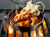 Prawn Makhani curry being cooked over hot charcoals.  Indian food recipe  pictures, photos & images