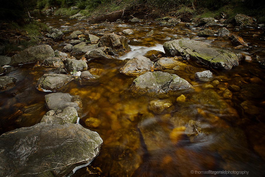 Rust coloured water flows over rocks in this picturesque mountain stream in the Wicklow Mountains