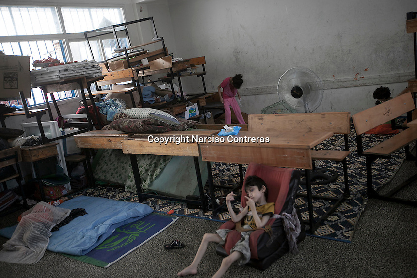 "In this Saturday, Aug. 16, 2014 photo, Mahmod 7 yo (front right), Malak 13 yo (back left), Hannan 14 yo (back right), and Nisma 22 yo (front left) are seen inside a classroom at the Al-Zaytoon UN School turned into a temporary refugee after their family fled from Shuyaja neighborhood when the IDF targeted and destroyed their house during the ""Protective Edge"" military operation in Gaza Strip. Mahmod, Malak, Hannan and Yussuf (not pictured) are four mental disable brothers and sisters of the father Jawal's family (not pictured), Nisma is a metal disable relative of them.  (Photo/Narciso Contreras)"