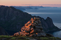 Summit cairn on Veinestind lit by setting sun, Moskenesøy, Lofoten Islands, Norway
