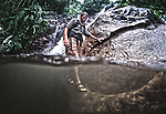 Shannon Walsh wades across a jungle pool while exploring Tioman Island off the coast of Malaysia.