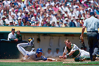 OAKLAND, CA - Roberto Alomar of the Toronto Blue Jays slides home safely as Oakland Athletics catcher Jamie Quirk applies a late tag during a game at the Oakland Coliseum in Oakland, California in 1991. Photo by Brad Mangin