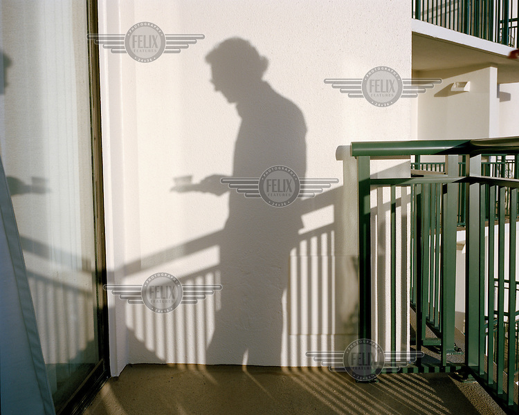 The shadow of a man holding a cup falls on a wall at a private party organised by the former students of the 1968 class of Balboa High School in the Panama Canal Zone, during the 2013 Panama Canal Society Reunion, at the Marriott hotel in Orlando, Florida.
