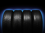 Set of four winter tires isolated on blue black background with clipping path