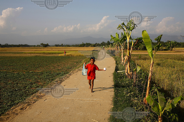 A chid walks down a road in Rajanagar built with the help of IFAD (International Fund for Agricultural Development).