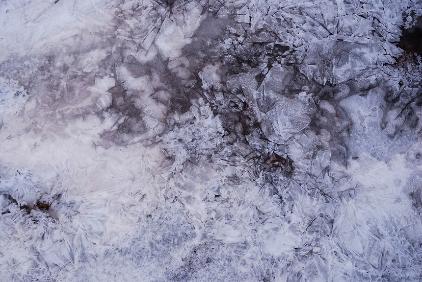 Geometric crackles emerge in the ice where bubbles have frozen on the creek on a icy morning.