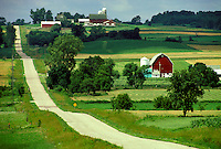 Country road through farm land with crops barns and houses Elsworth Wisconsin United States America USA