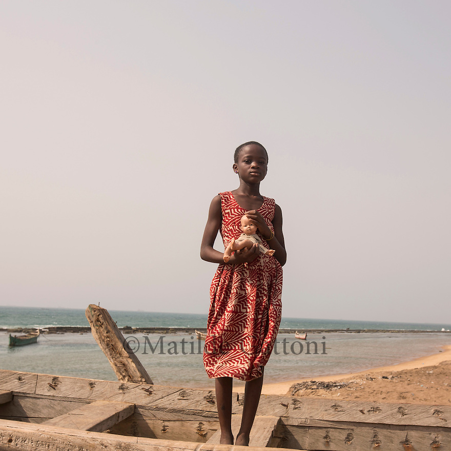Togo - Baguida - A little girl stands on a traditional fishing boat holding her doll. Baguida lies on the Togo coastline, few kilometers away from the capital Lome'. The town is experiencing massive coastal erosion, forcing the local population to relocate away from the sea.