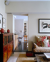 The living room of a Manhattan apartment is a tranquil oasis in muted shades of beige and contains an interesting collection of antique Chinese furniture and works of art