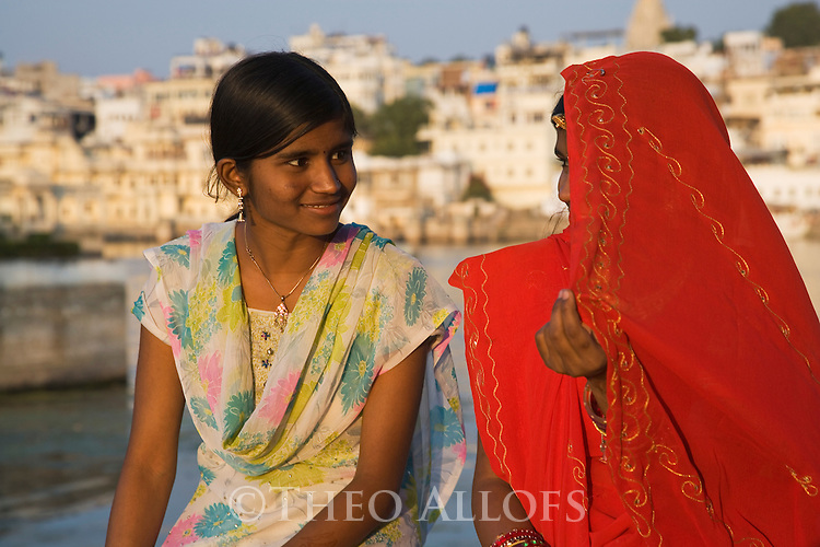 Rajasthani tribal girls sitting and talking on a wall of the city in the late afternoon; old town of Udaipur in background, Udaipur, Rajasthan, India --- Model Released