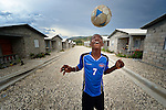 """A boy bounces a football on his head in a model resettlement village constructed by the Lutheran World Federation in Gressier, Haiti. The settlement houses 150 families who were left homeless by the 2010 earthquake, and represents an intentional effort to """"build back better,"""" creating a sustainable and democratic community."""