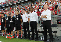 Toronto FC head coach Aron Winter and his coaching staff stand at attention during the national anthems in an MLS game between the FC Dallas and the Toronto FC at BMO Field in Toronto on July 20, 2011..FC Dallas won 1-0.