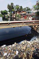 A polluted river runs through a central Jakarta slum.<br />