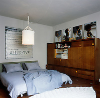 The main bedroom has a retro feel with a freestanding cupboard unit to one side. The double bed has grey blue bedding