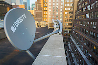 A DirecTV satellite dish on the rooftop of a building in New York on Thursday, July 21, 2016. (© Richard B. Levine)