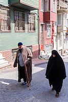Muslim man wearing traditional clothing woman in niqab veil  in area of Kariye Muzesi, Edirnekapi, Istanbul, Republic of Turkey