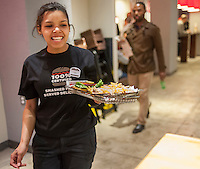 A server brings an order to the table at the new Smashburger restaurant in the shadow of the Empire State Building in New York on its grand opening day, Thursday, April 10, 2014. The popular Colorado chain, which has a cultish following, opened its first Manhattan outpost  bringing their burgers, smashed to order to the Big Apple. The fast casual restaurant has a loyal fan base and has 260 restaurants worldwide. The franchise welcomed their Manhattan customers by offering a free Classic Smashburger to each patron all day, with the line eventually stretching around the block.  (© Richard B. Levine)