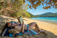 Young woman reading at Governors Bay in Marlborough Sounds, Nelson Region, Marlborough, South Island, New Zealand