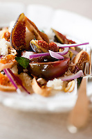 Close up of a colourful Panzanella, a typical Italian salad served with chunky bread crums, reinterpreted here with slices of fresh and dried figs mixed with fresh red onions