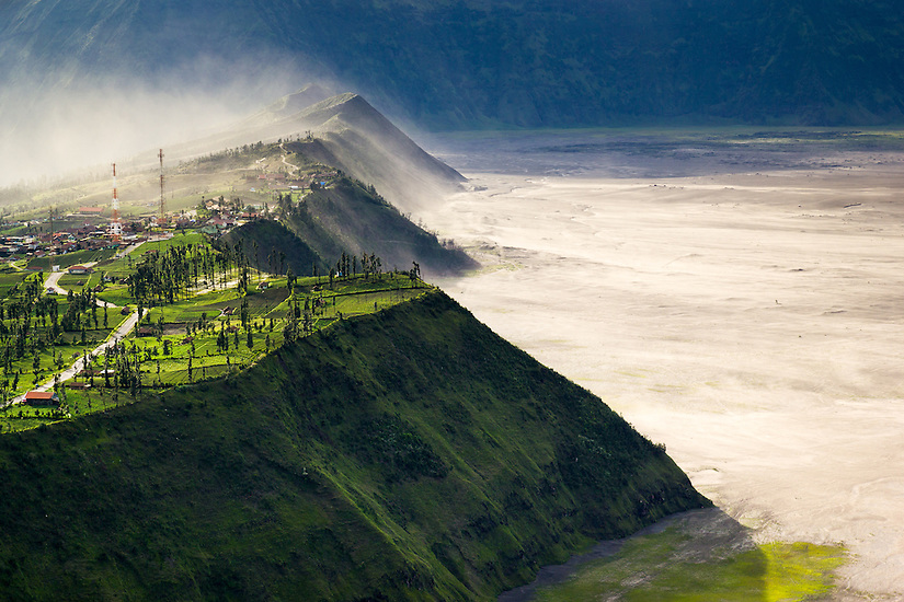 Volcanic ash from Mount Bromo blows over the Tengger caldera wall.