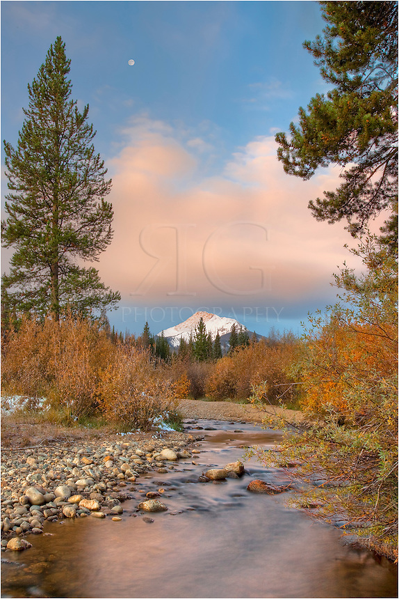 Byers Peak is majestic in the morning hours. This Colorado image was captured looking up St. Louis Creek outside of Fraser, Colorado. The morning clouds were breaking up and the moon was setting in the west.