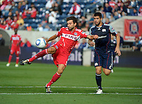 Chicago midfielder Baggio Husidic (9) shoots the ball in front of New England defender Franco Coria (2).  The Chicago Fire defeated the New England Revolution 3-2 at Toyota Park in Bridgeview, IL on Sept. 25, 2011.