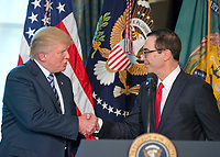 United States President Donald J. Trump shakes hands with US Secretary of the Treasury Steven Mnuchin prior to signing three Executive Orders concerning financial services at the Department of the Treasury in Washington, DC on April 21, 2017.<br /> Credit: Ron Sachs / Pool via CNP /MediaPunch