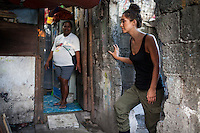 UK celebrity Myleene Klass stands over babie's grave headstones as she speaks with Rose Marie Ferrer, 33, at the entrance to Rose's house, where she lives with her large family, built over children's graves in an inhabited cemetery in Paranaque City, Metro Manila, The Philippines on 18 January 2013. Rose owns a shop in the cemetery where she sells funeral items. She supports her family with this, has breastfed all her 5 children, and is 9 months pregnant now. Photo by Suzanne Lee for Save the Children UK