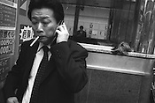 Salaryman smoking and speaking on his mobile telephone, beside a discarded wig, in Shibuya, Japan.