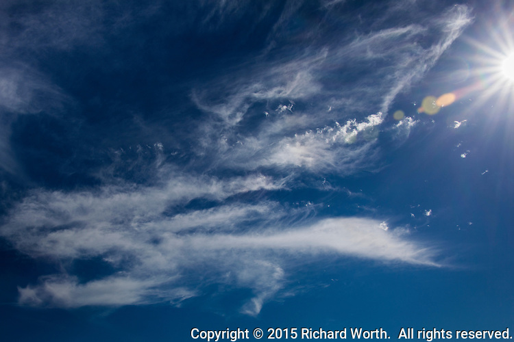 Cirrus clouds drift across a blue sky punctuated by a sun-burst.