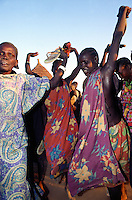 Sudan. South Sudan. Bahr El Ghazal. Anguoth. Dinka women celebrate holding their hands at arm's length the return of a slaved woman who was bought back by Christian Solidarity International (CSI) from arab traders. © 1999 Didier Ruef