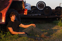 Good looking twenty something year old man in a black tee shirt and jeans outdoors at sunset in a car junk yard