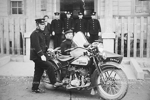 Sitting on new Harley-Davidson in front of entrance at Tokyo police Dept