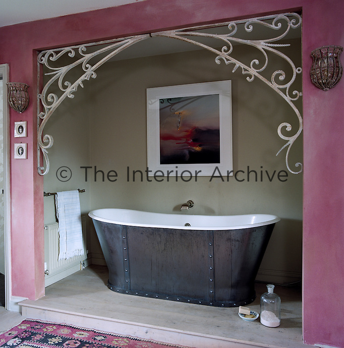 In the master bedroom an old-fashioned free-standing bath is theatrically situated on its own stage framed with wrought-iron curlicues