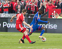 Toronto, Ontario - April 12, 2014: Colorado Rapids forward Edson Buddle #9 and Toronto FC defender Steven Caldwell #13 in action during the 2nd half in a game between the Colorado Rapids and Toronto FC at BMO Field in Toronto.<br />