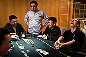 Chinese poker players share a light moment on the poker table at the Galaxy Macau Hotel in Macau, China.