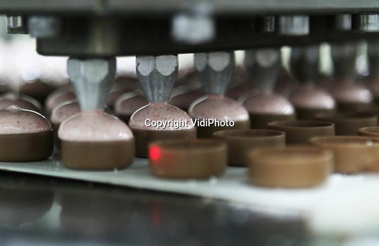 Foto: VidiPhoto..ESSEN - Bij de Nederlands-Belgische chocoladefabriek Ickx in Essen (B) bij Roosendaal (Nl) rollen de lekkerste chocoladeproducten over de lopende band. De chocoladespecialist, levert onder private label aan diverse Nederlandse supermarkten levert. De vraag naar de deels handgemaakte chocoladeproducten van de fabriek-met-drie-gezichten (Ickx, Dragee en Rosenberg)  is zo groot, dat de chocolatterie vorig jaar een omzetstijging van 11 procent wist te boeken. Een deel van de bonbons en andere chocoladeproducten wordt gevuld met handgemaakte Nederlandse jam. Foto: De vulling wordt machinaal aangebracht..