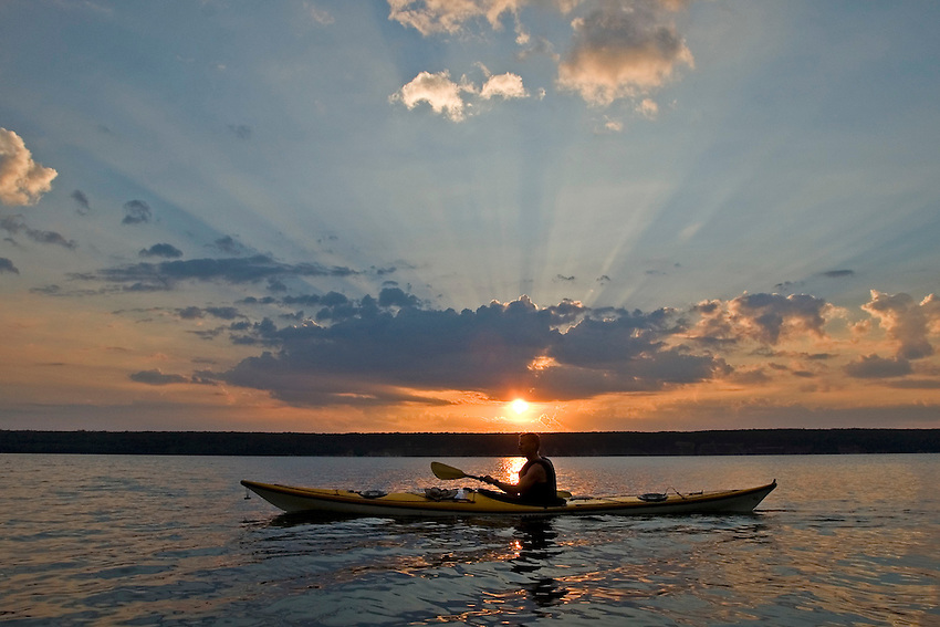 The setting sun bursts through clouds behind a sea kayaker paddling at Grand Island National Recreation Area in Munising Michigan.