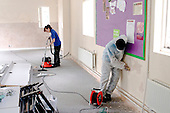 Premises staff, with vacuum cleaner, and Work Experience student refurbishing a room,  State Secondary Roman Catholic school.