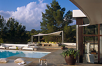 Raised sunbathing platforms with large cushions are positioned around the swimming pool