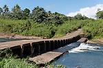 Rakiraki, Viti Levu, Fiji; a concrete bridge crosses a river on the road to a local village, as women do laundry in the water
