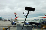 Telescopic window washing pole reaches on to 2nd storey arrivals glass near 747 at Heathrow Airport's T5