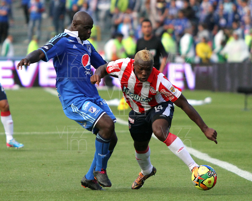 BOGOTA -COLOMBIA. 11-05-2014. Modeste M´Bami (Izq) de Millonarios  disputa el balon contra Edison Toloza   del Atletico Junior  partido de vuelta por la Semifinal  de La liga Postobon  disputado en el estadio Nemesio Camacho El Campin. / Modeste M´Bami  of Millonarios (L) to dispute the balloon against  Edison Toloza  of Atletico Junior  second leg of the semifinals of the league Postobon played at Estadio Nemesio Camacho El Campin. Photo: VizzorImage/ Felipe Caicedo / Staff
