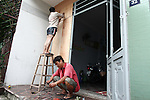 Two men board up the windows of a house in Da Nang, Vietnam Saturday in preparation for Super Typhoon Haiyan, expected to hit the city around 4 a.m. Sunday morning. Local authorities announced they were evacuating 20,000 people in vulnerable areas in advance of the storm and advised others to stay inside their houses.