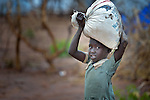 A girl carries a bag of grain in the Ajuong Thok Refugee Camp in South Sudan. The camp, in northern Unity State, hosts thousands of refugees from the Nuba Mountains, located across the nearby border with Sudan. The ACT Alliance provides a variety of services in the camp.